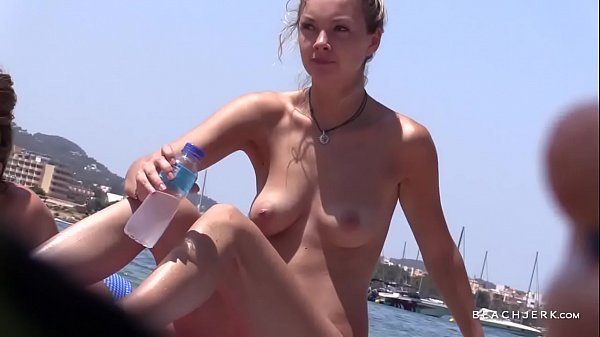 Two hot blonde babes compare their perfect tits on the topless beach